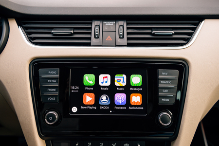 radio unit: PARIS, FRANCE - DEC 13, 2016: Apple CarPlay main screen in modern car dashboard. CarPlay is an Apple standard that enables a car radio or head unit to be a display and controller for an iPhone. It is available on all iPhone 5 and later with at least iOS 7