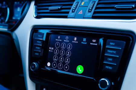 radio unit: PARIS, FRANCE - DEC 13, 2016: Apple CarPlay phone main screen in modern car dashboard in blue background tone. CarPlay is an Apple standard that enables a car radio or head unit to be a display and controller for an iPhone Editorial