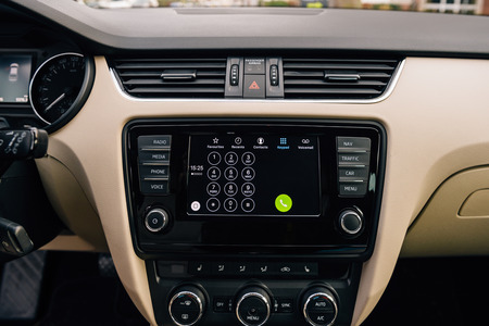 enables: PARIS, FRANCE - DEC 13, 2016: Apple CarPlay phone main screen in modern car dashboard. CarPlay is an Apple standard that enables a car radio or head unit to be a display and controller for an iPhone. It is available on all iPhone 5 and later with at least