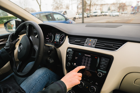 radio unit: PARIS, FRANCE - DEC 13, 2016: Woman driving dialing number on the Apple CarPlay main screen in modern car dashboard. CarPlay is an Apple standard that enables a car radio or head unit to be a display and controller for an iPhone. It is available on all iP Editorial