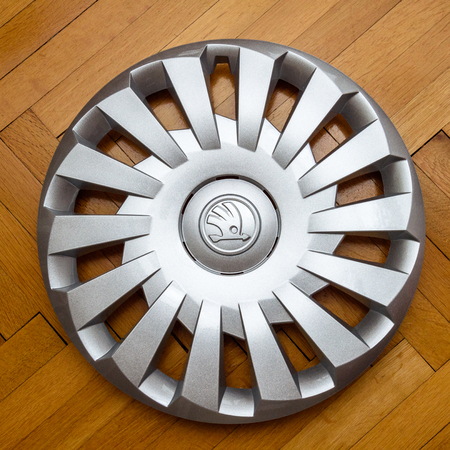 hubcaps: PARIS, FRANCE - DEC 18, 2016: Modern hubcap hub cover for the winter tyre made by Skoda Auto for Skoda Superb, Skoda OCtavia and Skoda Roomster  on wooden background