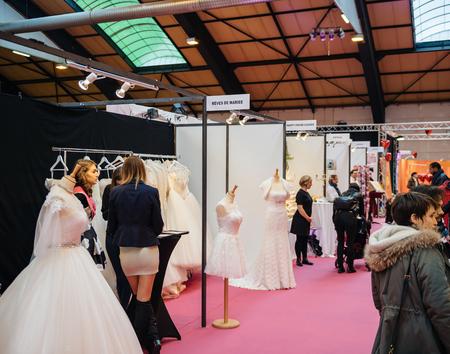 STRASBOURG, FRANCE - JAN 8, 2017: Wedding dresses and cocktail fashion dress at the Wedding fair waiting for customers Redakční