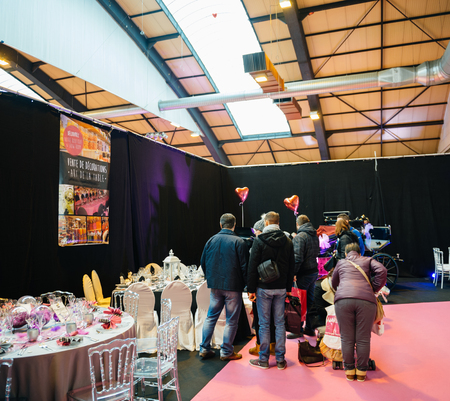 upcoming: STRASBOURG, FRANCE - JAN 8, 2017: Family admiring table setting and luxury decorations at the wedding fair  for the upcoming event Editorial
