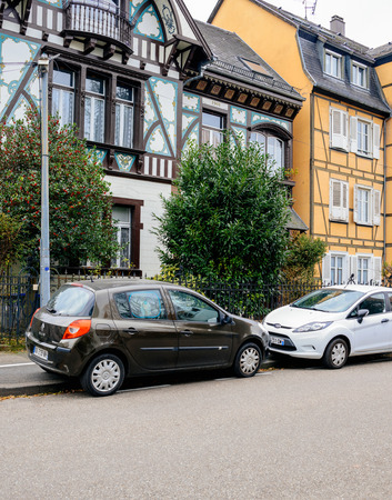STRASBOURG, FRANCE - DEC 2, 2016: Renault Clio and Ford Fiesta in front of beautiful timbered house in Alsatian style in Strasbourg, France Editorial