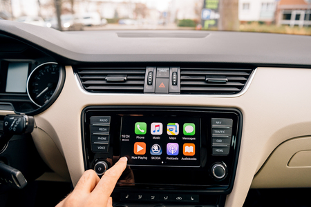 radio unit: Man pressing home button on the Apple CarPlay main screen in modern car dashboard. CarPlay is an Apple standard that enables a car radio or head unit to be a display and controller for an iPhone. It is available on all iPhone 5 and later with at least iOS