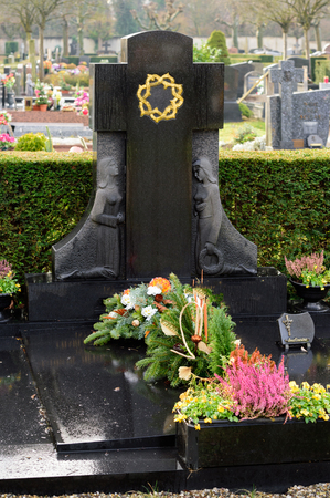 Black marble tombstones in French cemetery with beautiful crafted crosses and golden sign