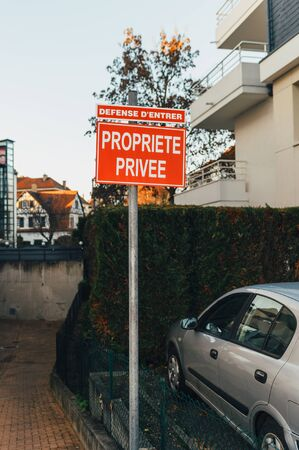 no trespassing: Propriete Privee - Private Property translated from French - with house, garden and parked car in French city