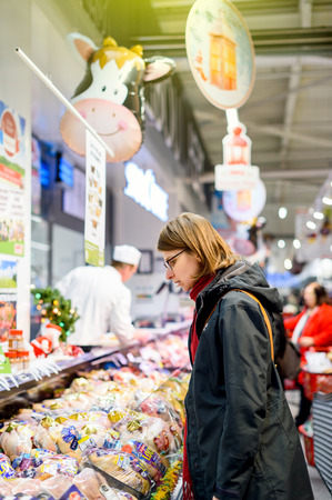 STRASBOURG, FRANCE - 21 DEC 2016: Woman selecting then purchasing fresh raw meat chicken ,pork, beef and duck at French supermarket