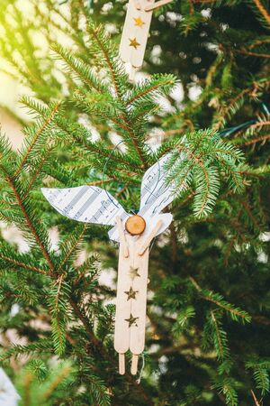 Hand-made Christma angel on green fir tree seen at the traditional Christmas market in Thann, France