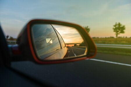 rearview: Vintage look of road and trees reflected in rear-view mirror while driving through agricultural field