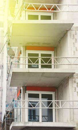 Modern apartment construction with new PVC windows and protection fence for the workers and beautiful son flare Stock Photo