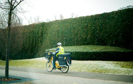 STRASBURGO, FRANCIA - 30 DICEMBRE 2016: Operaio postale sulla bicicletta elettrica che consegna posta - ciclando velocemente