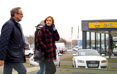gro: STRASBOURG, FRANCE - DEC 21, 2016: Father and daughter in front of Opel showroom in city with cars presented outside car dealer. Adam Opel AG is a German automobile manufacturer headquartered in Rüsselsheim, Hesse, Germany, subsidiary of the American gro Editorial