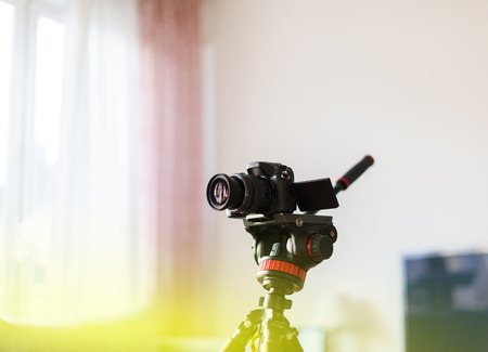 Video camera on tripod in home environment - modern technology used by influencer vlogger for live transmission through social network and online streaming