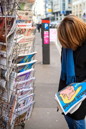 PARIS, FRANCE - JAN 21, 2017: Woman purchases Charlie Hebdo, Le Monde newspaper from a newsstand featuring headlines with Donald Trump inauguration as the 45th President of the United States in Washington, D.C