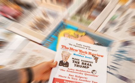 above 21: PARIS, FRANCE - JAN 21, 2017: Man holding The New york Review above major international newspaper journalism featuring headlines with Donald Trump inauguration as the 45th President of the United States in Washington, D.C