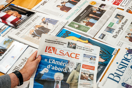 above 21: PARIS, FRANCE - JAN 21, 2017: Man holding LAlsace  above major international newspaper journalism featuring headlines with Donald Trump inauguration as the 45th President of the United States in Washington, D.C