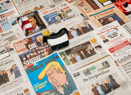 above 21: PARIS, FRANCE - JAN 21, 2017: Virtual Reality Mask above major international newspaper journalism Financial Times featuring headlines with Donald Trump America First at inauguration as the 45th President of the United States in Washington, D.C