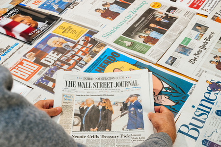PARIS, FRANCE - JAN 21, 2017: Man holding The Wall Street Journal above major international newspaper journalism featuring headlines with Donald Trump, Barack Obama, Melania Trump and Michele Obama inauguration as the 45th President of the United States i