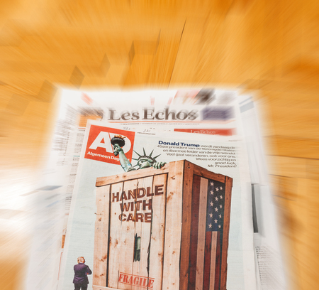above 21: PARIS, FRANCE - JAN 21, 2017: Algemeen Dagblad Dutch magazine above major international newspaper journalism featuring portrait of Donald Trump inauguration as the 45th President of the United States in Washington, D.C