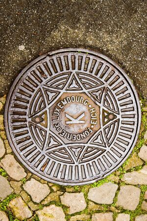 Fonderie de Luxembourg translating as Luxembourg Foundry - manhole cover surrounded by old cobblestone Editorial