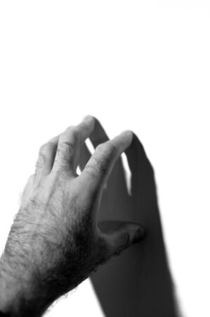 existent: Mans hand touching the white wall - conceptual image of escape, touching the in existent and getting in the outer world Stock Photo