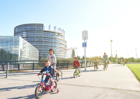 STRASBOURG, FRANCE - AUG 20, 2015: Young kids and adult people having fun on bicycles biking sporting in front of the European Parliament  building on a peaceful sunny summer day in Strasbourg, european Capital Editorial