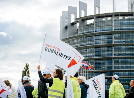 STRASBOURG, FRANCE - OCT 7, 2015: Rear view of tobacconists buralistes people protesting in front of the European Parliament building with flags placards while President Francois Hollande is entering the Parliament gates Confederation des buralistes
