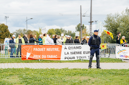 protestors: STRASBOURG, FRANCE - OCT 7, 2015: Police officer surveilling tobacconists buralistes people protesting at European Parliament building with flags placards while French President enters the Parliament gates Confederation des buralistes