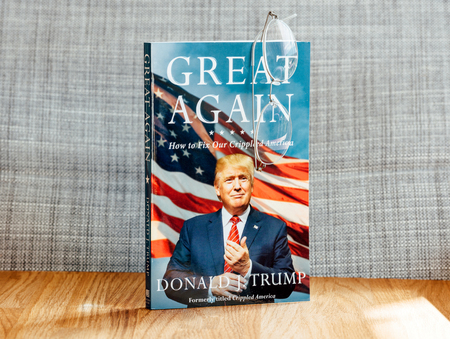 senate race: PARIS, FRANCE - FEB 9, 2017: Great Again - how to fix our crippled America biography book by Donald J Trump with reader classic vintage eyeglasses as a bookmark. Crippled America: How to Make America Great Again is a book by Donald Trump, published by Sim Editorial