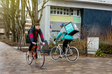 STRASBOURG, FRANCE -FEB 4, 2017: Deliveroo biker cycling fast on rainy day to deliver on time the food to the client. Deliveroo is a British online food delivery company with operations spread across eighty-four cities in the UK, the Netherlands, France,