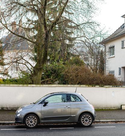 STRASBOURG, FRANCE - FEB 12, 2017: Elegant Italian Fiat Cinquecento mini compact electric car parked in city near a beautiful house Editorial