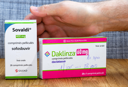generic medicine: PARIS, FRANCE - FEB 9, 2017: Male hand above Sovaldi 12-week treatment costs $84,000 in the United States and Daklinza cost $63,000 medications to treat hepatitis C (HCV)