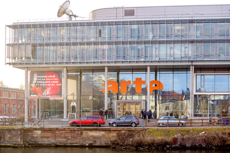 promotes: STRASBOURG, FRANCE - FEB 2, 2017: Arte (Association Relative A la Television Europeenne) television headquarter in Strasbourg with Programme advertising banner on facade. ARTE is a Franco-German TV network, a European channel, that promotes programming in