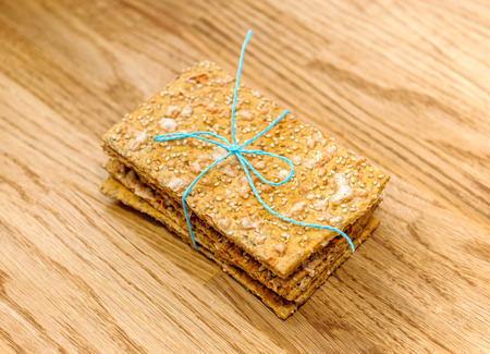 Delicious crispread tied with organic blue thread on wooden oak table