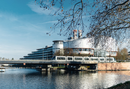 STRASBOURG, FRANCE - DEC 25, 2015: Large building of the European Court of Human Rights building in Strasbourg, France on a warm winter day and Ill river. ECHR is a international court established by the European Convention on Human Rights.