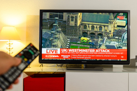 counter terrorism: PARIS, FRANCE - MARCH 22: Man holding remote control watching BBC  channel reporting live scenes from Westminster Bridge after armed attack on March 22 in London. A police officer has been stabbed near to the British Parliament Editorial