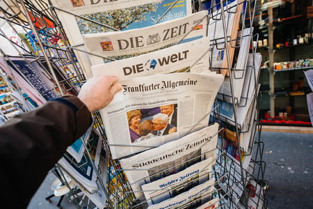 law breaking: PARIS, FRANCE - MAR 23, 2017: Man purchases a German Frankfurter Allgemeine Zeitung newspaper from press kiosk newsstand featuring headlines following the terrorist incident in London at the Westminster Bridge Editorial