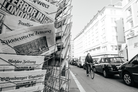 law breaking: PARIS, FRANCE - MAR 23, 2017: Senior cyclist woman passing near Suddeutsche Zeitung and other international magazines covers at press kiosk newsstand featuring headlines following the terrorist incident in London at the Westminster Bridge
