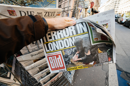 law breaking: PARIS, FRANCE - MAR 23, 2017: Man purchases a   newspaper German Bild from press kiosk newsstand featuring Terror in London headlines following the terrorist incident in London at the Westminster Bridge
