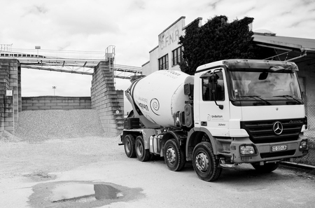 beton: STRASBOURG, FRANCE - JUN 19, 2016: Black and white of Mercedes-Benz Actros concrete truck from UNIBETON factory, member of Italcementi Group in front of modern Beton Concrete Factory on a summer day Editorial