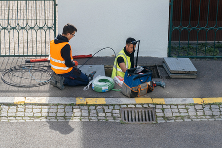 PARIS, FRANCE - MAR 24, 2017: Team of workers from telecomunication internet provider company working on implementation of fiber optic cables in sewage system - aerial view