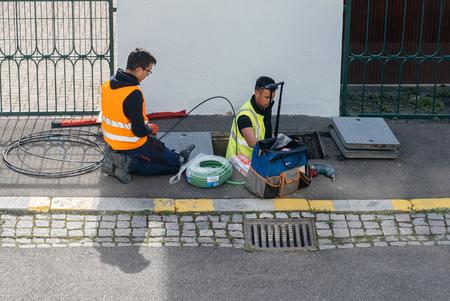 PARIGI, FRANCIA - 24 MARZO 2017: Squadra di operatori della telecomunicazione società di servizi Internet che lavorano sull'implementazione dei cavi in ??fibra ottica nel sistema fognario - vista aerea