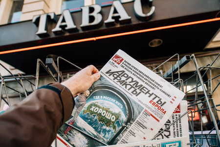 PARIS, FRANCE - MAR 23, 2017: Man purchases Argumenty i Fakty russian newspaper from press kiosk newsstand featuring headline Where in Russia is ok to live Editorial