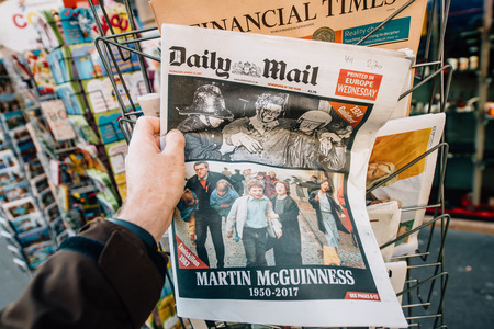 northern ireland: PARIS, FRANCE - MAR 23, 2017: Man purchases Daily Mail newspaper from press kiosk newsstand featuring James Martin Pacelli McGuinness tribute. He was an Irish republican and Sinn Féin politician who was the deputy First Minister of Northern Ireland Editorial