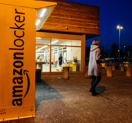 PARIS, FRANCE - FEB 15, 2017: Woman leaving Amazon locker orange delivery package locker at dusk - Amazon Locker is a self-service parcel delivery service offered by online retailer Amazon.com. Amazon customers can select any Locker location as their deli