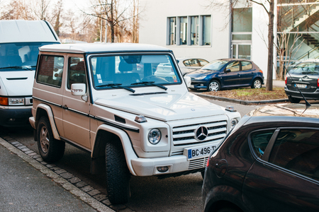 ag: STRASBOURG, FRANCE - FEB 13, 2017: Front of luxury white Mercedes-Benz G-Class suv parked on French street.