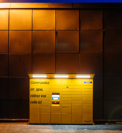 PARIS, FRANCE - FEB 15, 2017: Square image of Amazon locker orange delivery package locker at dusk - Amazon Locker is a self-service parcel delivery service offered by online retailer Amazon.com. Amazon customers can select any Locker location as their de