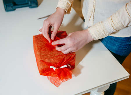 Creative woman working on her hoppby at home - wrap gift cutting red silkl - wrapping gift for the upcoming holidays and anniversaries - hand made manufacture for birthday, Christmas,
