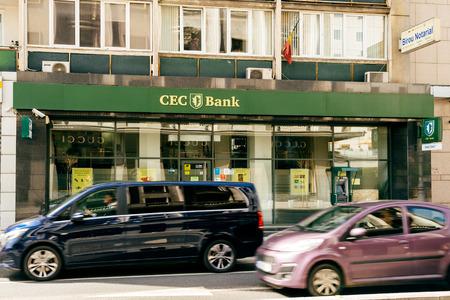 BUCAREST, ROMANIA - 1 APRILE 2016: Automobili che guidano velocemente sul boulevard di Bucarest con l'agenzia bancaria della CCE nei precedenti. CEC Bank è un'istituzione bancaria rumena statale Archivio Fotografico - 74754513